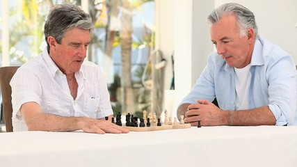 Elderly men playing chess in a nursing home