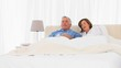 Mature couple watching tv in the bed