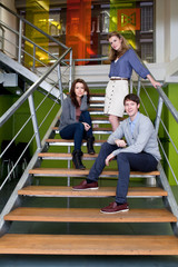 Man and two women on stairs in office