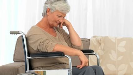 Elderly woman in a wheelchair thinking