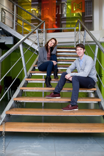 Man and woman sitting on stairs in office