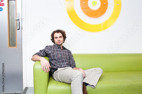Young man sitting on couch in office
