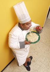 Cocinero comiendo pasta de pie.