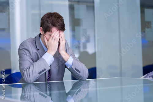 Depressed businessman sitting at conference table