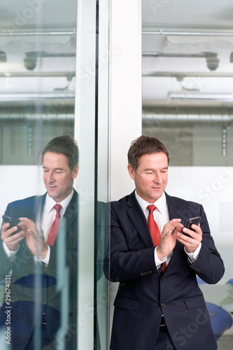 Businessman sending a text message