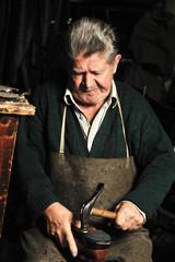 Elderly man, shoemaker repairing old shoe in his workshop