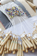 Close-up of lace-making pin cushion. Pins and wooden bobbins.