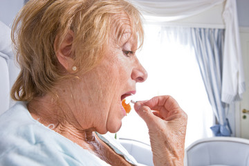Elder woman taking a pill