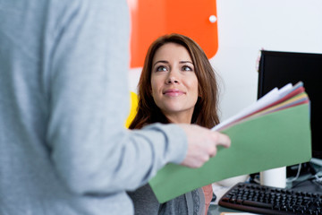 Man giving documents to woman at desk