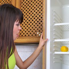 Young woman looks into the empty fridge