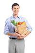 Smiling shopping man holding bag with fruits and vegetables