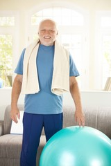Active senior exercising with fit ball