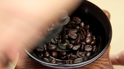 Coffee beans being ground in an old fashioned coffee grinder.