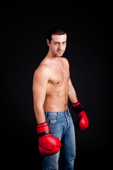 Young man with boxing gloves isolated on black