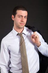Confident businessman holding jacket over his shoulder