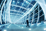 Fototapety People walking in modern blue walkway interior