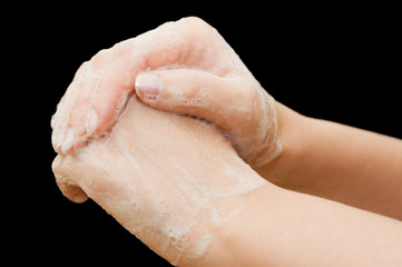 Female hands in soapsuds on black background