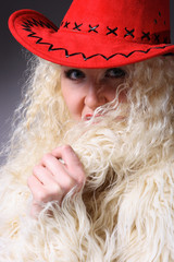 Curly blonde in a red hat and white fluffy fur coat