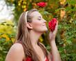 Frau im Garten riecht an den Rosen