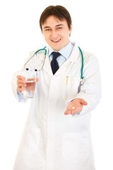 Smiling  medical doctor with drug and glass of water in hands
