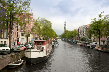 Typical Amsterdam's canal with and boats parked along it