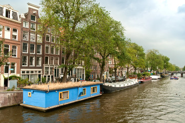 Typical Amsterdam's canal with blue house boat (houseboat)