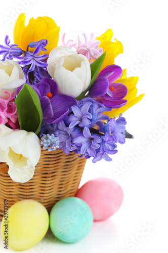 beautiful bouquet of spring flowers in basket with easter eggs o