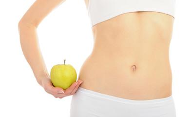 woman with beautiful body holding an apple near the slim waist.