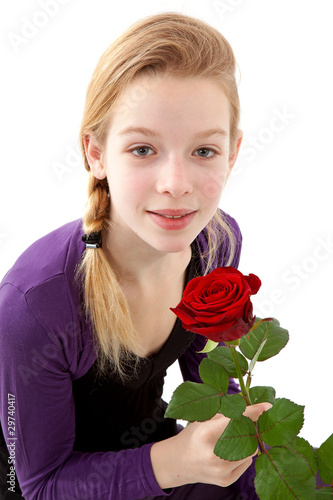 Leinwanddruck Bild young girl posing with red rose over white background