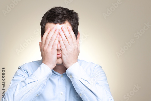 Dramatic portrait of desperated sad man in pain hiding his face