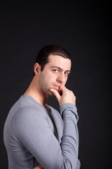Thoughtful young man on dark background
