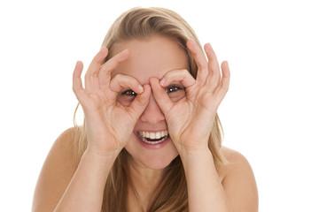 Junge freundliche Frau macht Brillensymbol