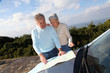 Senior couple looking at road map on car hood