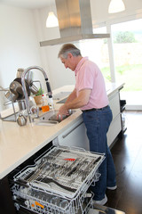 Senior man doing the dishes