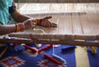 canvas print picture - Woman hand weaving a carpet with a manual loom in India