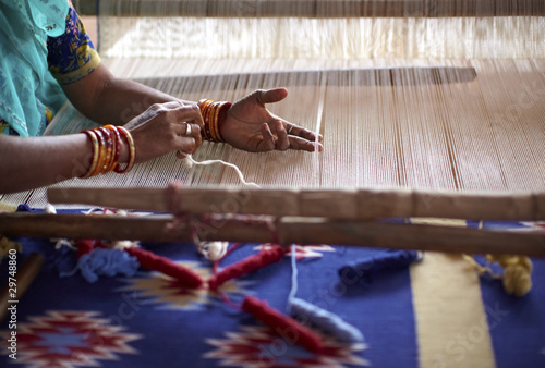canvas print picture Woman hand weaving a carpet with a manual loom in India