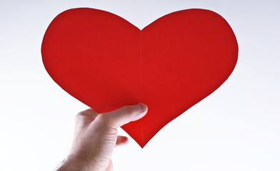 Hand with red paper heart