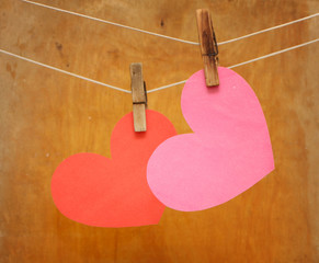 Hearts hanging on clothespins on a rope on a wooden background