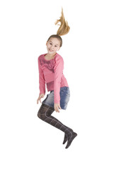 Young excited girl jumping up isolated on white background