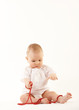 Cute baby girl playing with red beads