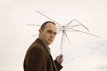 Man Holding Useless Umbrella