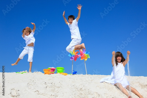 Children and pinwheels on sand