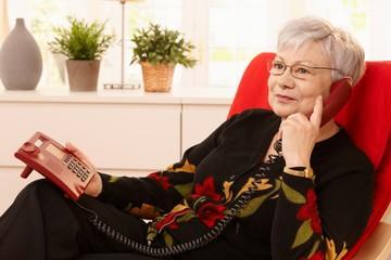 Pensioner woman using landline phone