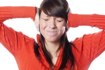 jeune femme grimaçant bouchant ses oreilles