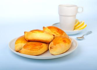 Tasty pies on plate, cup of tea with lemon and teaspoon.