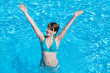 Young Happy Woman in Sunny Swimming Pool in Luxurious Hotel