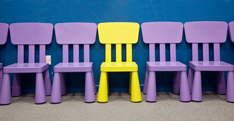 A yellow colored one in the middle of purple colored chairs