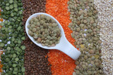 Ceramic spoon with lentils over seeds and grains background