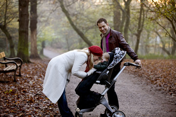 A young couple standing with a stroller in the park