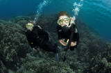 young boy scuba diver dives with mother poster